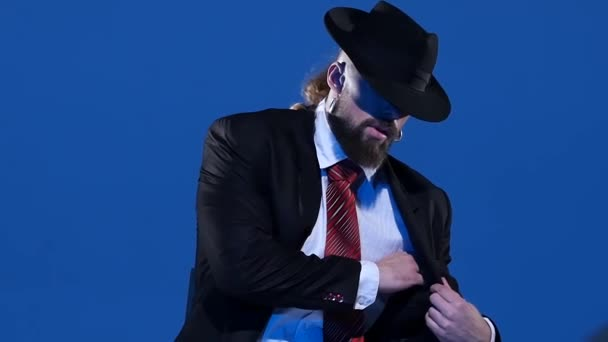 Elegantní muž v černém klobouku tančí erotický tanec. Spotlight na modrém pozadí. Zavřít, zpomalit..