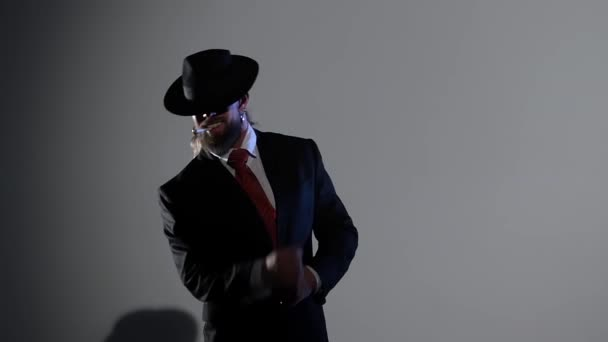 Elegantní muž v černém klobouku tančí erotický tanec. Spotlight na černém pozadí. Zavřít, zpomalit..
