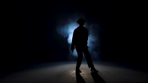 Silueta mladé tanečnice tančící stylově Michael Jackson na modrém pozadí kouře. Zavřít, zpomalit..