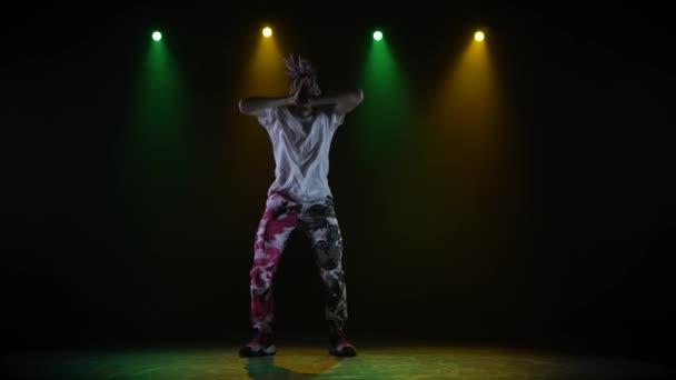 Profi fiatal hip-hop táncos, sötét stúdióban táncol a zöld és sárga ködben. Hip hop kultúra. Próba. Kortárs.