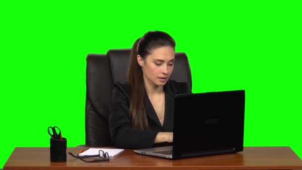 Girl enthusiastically works behind a laptop, smiles and enjoys the result. Green screen. Slow motion