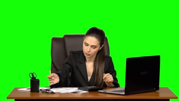 Obchodní žena na pracovišti se zabývá financemi, provádí výpočty na kalkulačce a vyplňuje papíry. Zelená obrazovka