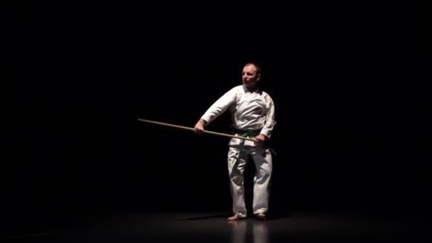 Kendo bojovník na bílém kimonu cvičí bojové umění s bambusovým bokken na černém pozadí. Zpomalený pohyb