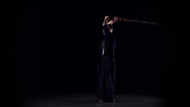 männliche Kendo-Kriegerin, die Kampfkunst mit dem Bambusbokken auf schwarzem Hintergrund praktiziert. Zeitlupe