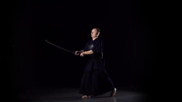 Kendo bojovník cvičit bojové umění s Katana meč na černém pozadí. Zpomalený pohyb