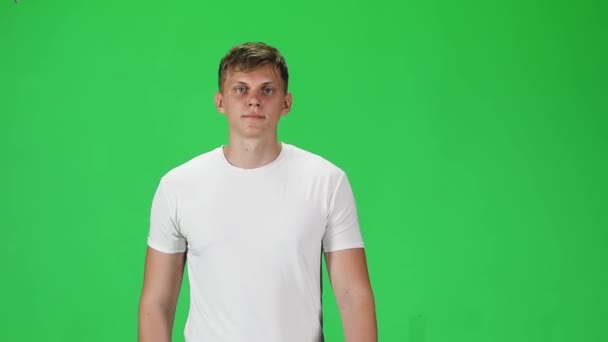 Young man in a white t-shirt going and looking forward against a green background. Slow motion.