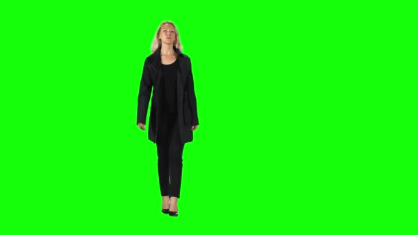 Blonde girl in black coat, trousers and high-heeled shoes going against a green screen.