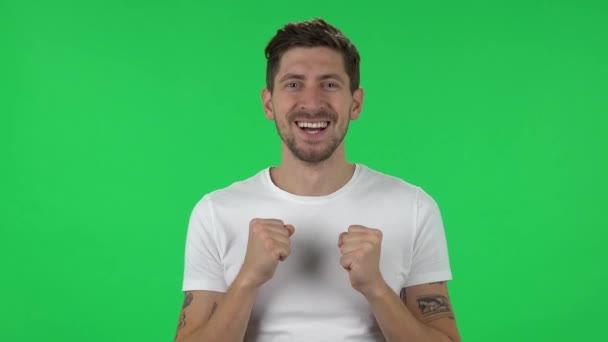 Portrait of confident guy is looking straight and rejoicing. Green screen