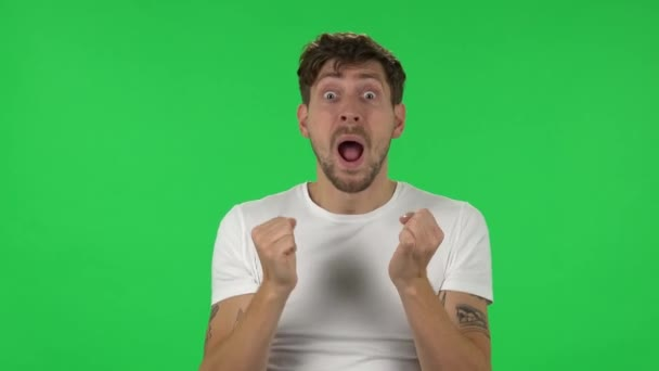 Portrait of confident guy with shocked surprised wow face expression is rejoicing. Green screen
