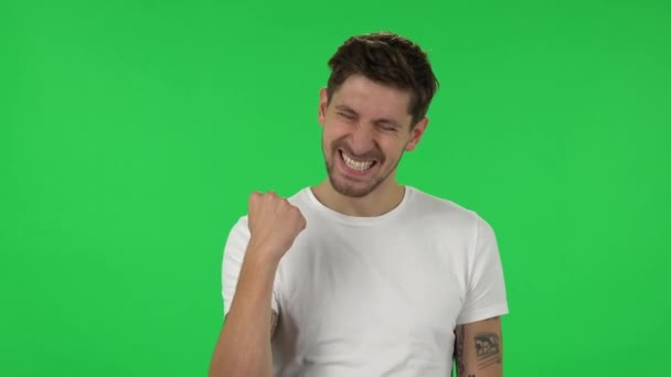 Portrait of confident guy is looking at the camera with excitement, then celebrating his victory triumph. Green screen