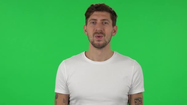 Portrét sebevědomého chlapa, který se dívá na kameru s očekávaným potěšením. Zelená obrazovka