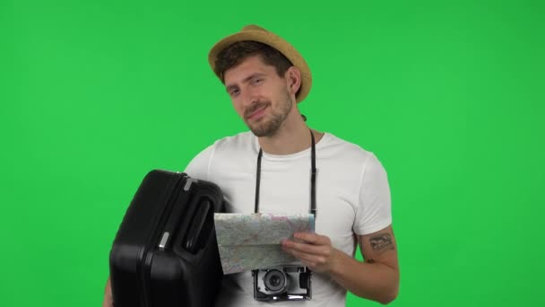 Portrait of tourist with suitcase in hand, retrocamera and map is looking at camera with seductive smile. Greenscreen