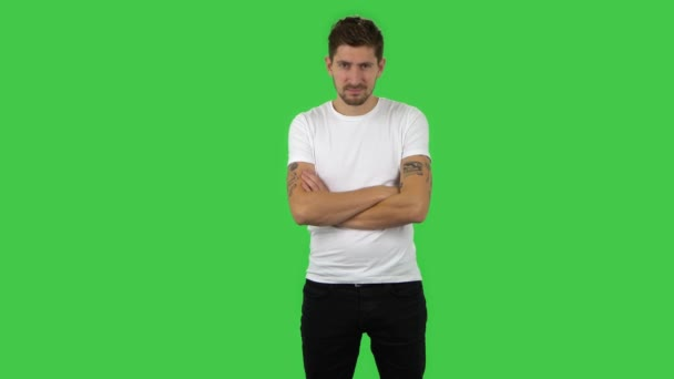 Confident guy is looking straight and crossing his arms over his chest. Green screen
