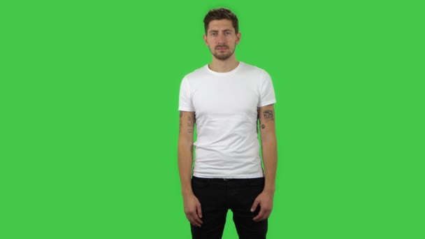 Confident guy is looking straight and smiling. Green screen