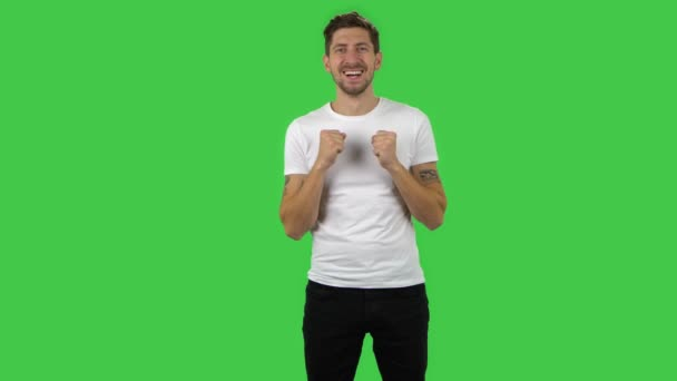 Confident guy is looking straight and rejoicing. Green screen