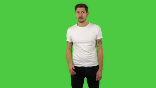 Confident guy is looking around, covering his mouth with his hand and whispering the secret. Green screen