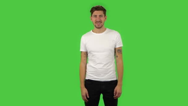 Confident guy is smiling and showing heart with fingers then blowing kiss. Green screen