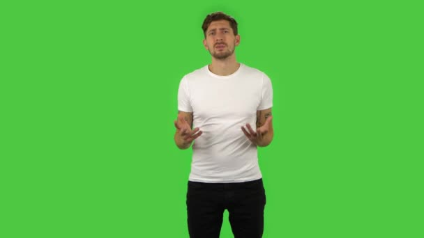 Confident upset guy is shrugging and sighing. Green screen