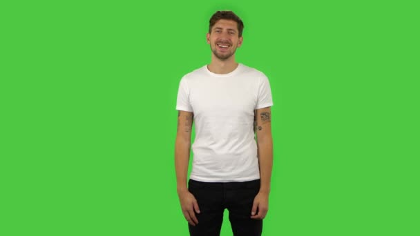 Confident guy is smiling broadly and winking. Green screen