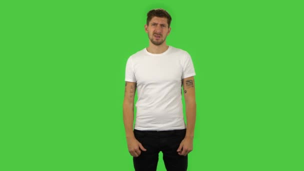 Confident guy is showing thumbs down gesture. Green screen