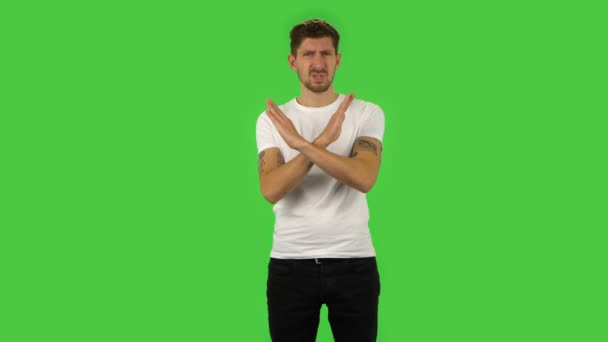 Confident guy strictly gesturing with hands crossed making X shape meaning denial saying NO. Green screen