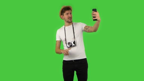 Sebevědomý chlap dělá selfie na mobilu a pak se dívá na fotky. Zelená obrazovka