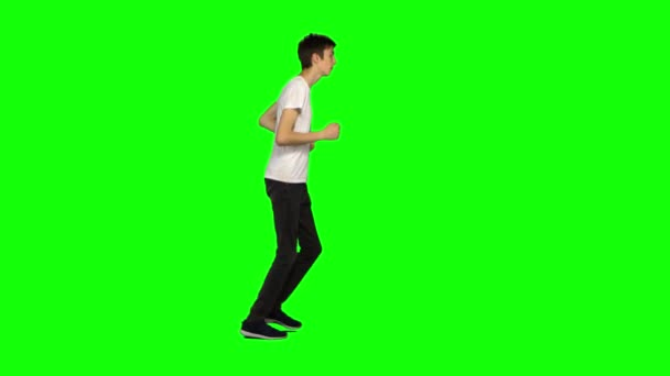 Tall skinny teen guy is running on green screen background. Chroma key, 4k shot. Profile view.