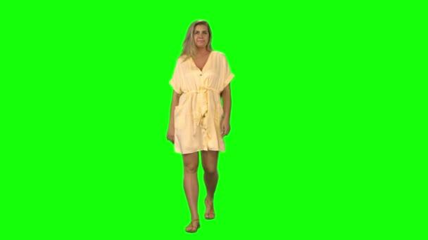 Vyčiněná blondýnka klidně kráčí a usmívá se na zelené obrazovce. Chromatický klíč, 4K výstřel. Pohled zepředu.