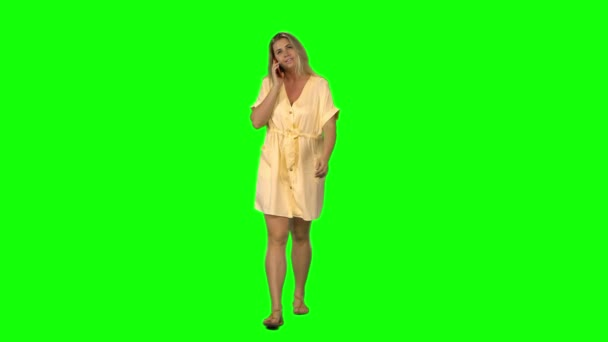 Tanned blond woman is calmly walking and talking on the mobile phone with smile on green screen. Front view.