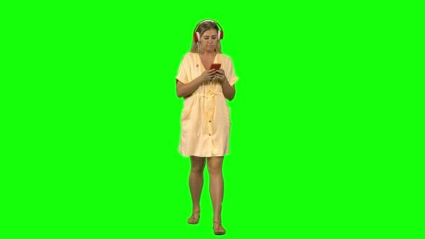 Vyčiněná blondýnka klidně chodí ve velkých červených sluchátkách, vybírá si hudbu na mobilním telefonu na zeleném plátně. Pohled zepředu