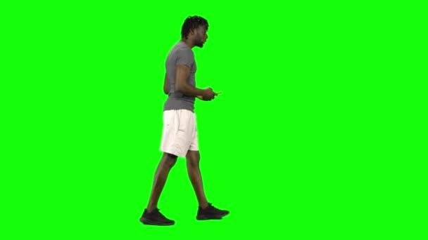 Afrikanischer Mann, der zu Fuß geht und SMS schreibt, wetteifert mit seinem Mobiltelefon am Green Screen, Chroma Key. Profilansicht.