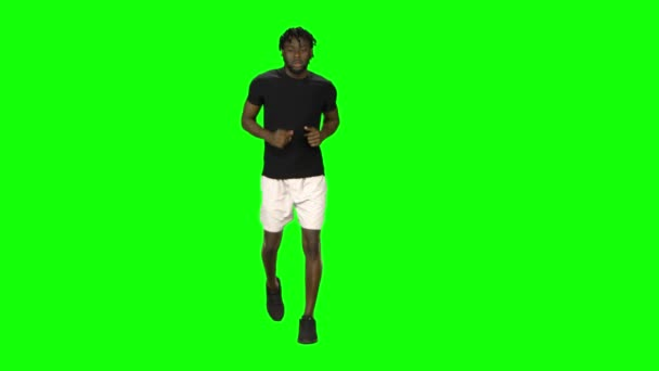 African american man is running at Green Screen, Chroma Key. Front view.