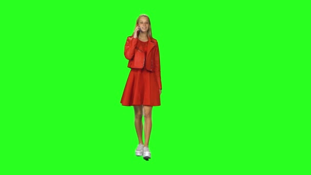 Blonde girl is calmly walking and talking on the mobile phone at green screen background. Chroma key. Front view.
