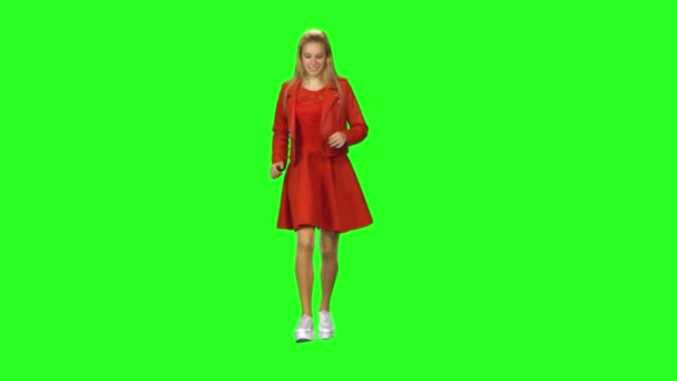 Blondes Mädchen läuft zu einem Treffen mit lieblichem Lächeln auf grünem Bildschirmhintergrund. Chroma-Taste, 4k Schuss. Frontansicht.