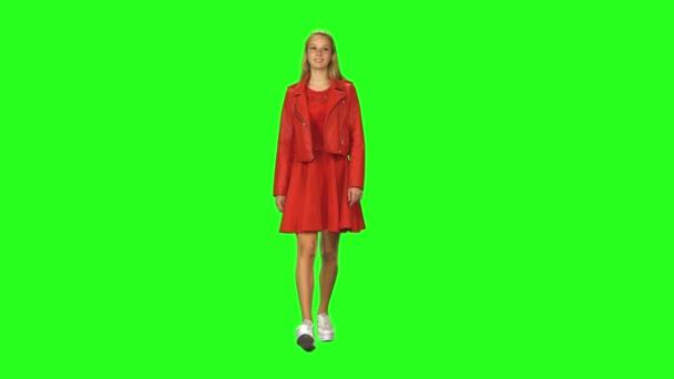 Blondes Mädchen, das ruhig auf grünem Bildschirmhintergrund geht. Chroma-Taste, 4k Schuss. Frontansicht.