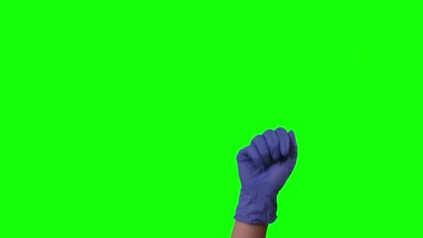 Az orvosok női kéz kék kesztyűben szimbolikus gesztusokat tesznek, rámutatva valamire. Zöld vászon. Közelről.