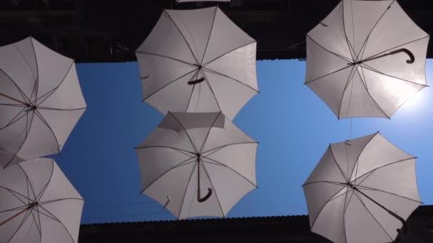 Weiße Regenschirme hängen an Seilen zwischen alten Gebäuden und wiegen sich im Wind. Umbrella Sky Project. Blauer Himmel, strahlende Sonne in Catania, Sizilien, Italien