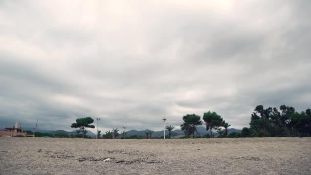 Malebná krajina. Hory, palmy, budovy a zatažená obloha. Sicílie, Itálie