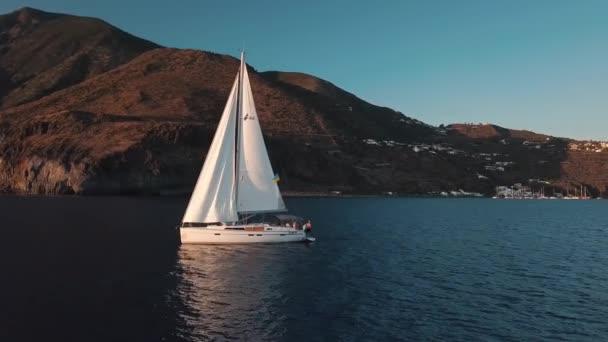 Letecký pohled na plachetnici s lidmi na palubě. Ukotvené ve Středozemním moři poblíž ostrova Lipari s přístavem a budovami na něm. Sicílie, Itálie