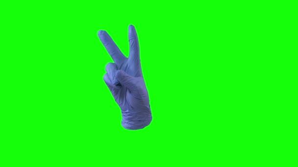 Az orvosok női kéz kék kesztyűben két ujjnyi győzelmi jelet mutatnak. Zöld vászon. Közelről.