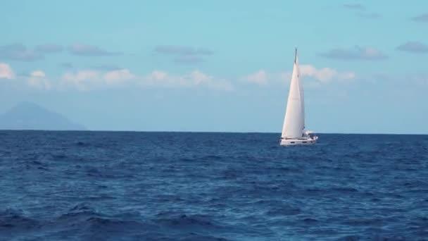 Bílá plachetnice plachtění v moři proti modré obloze a horách