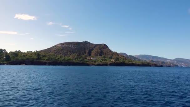 Blick vom fahrenden Boot auf Berge, Meer und blauen Himmel