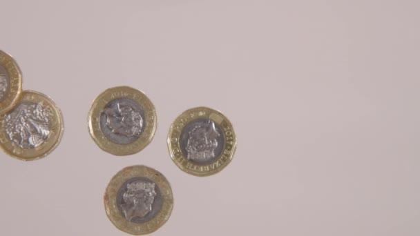 Červí oko zpomaluje záběr někoho, kdo přehazuje pár liber mincí přes skleněný stůl