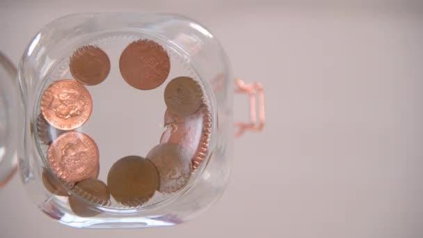 Pohled na červí oko, jak někdo shazuje mince do sklenice.