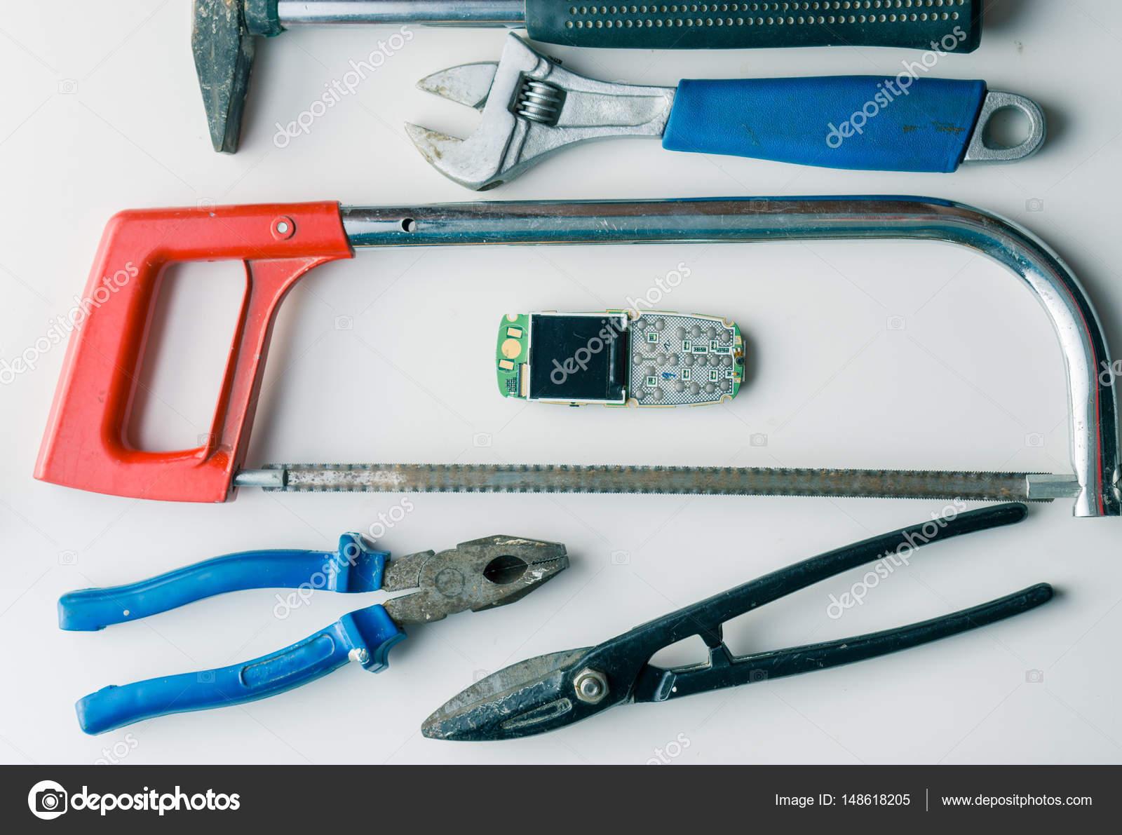 Cassé téléphone portable sur le bureau blanc avec mauvais outils