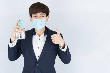 Asian handsome happy business man wearing a medical protection face mask for protect the coronavirus, filter dust PM 2.5 and cold and showing sanitizer hand gel and thumbs up on white background