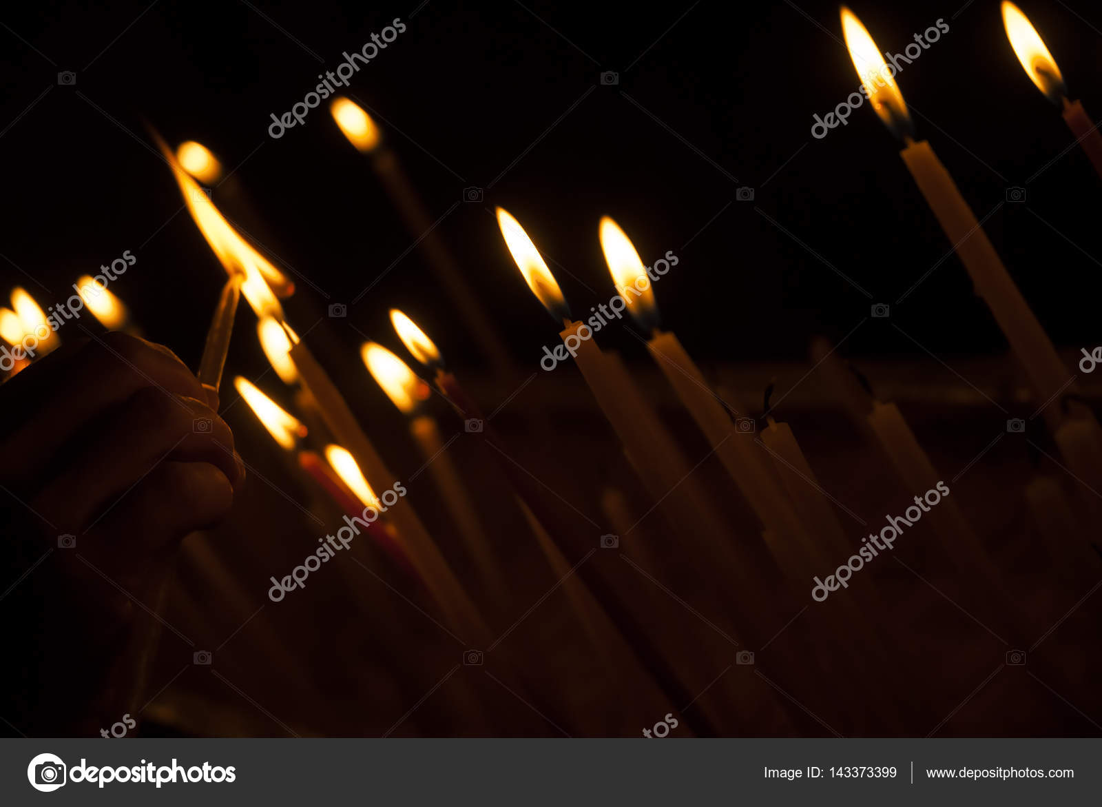 Woman hand lighting candles in a church Candles and the hand putting a new candle & Woman hand lighting candles in a church Candles and the hand ...