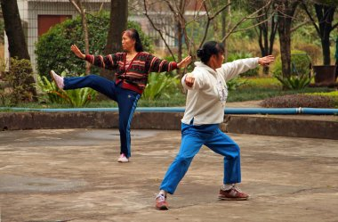 GUILIN, CHINA - NOV 4, 2007: Chinese women doing tai chi in the park. Tai Chi, Wushu and other health practices outdoors - this is a very popular activity among all ages in China