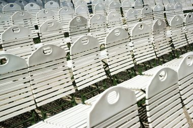 Rows of white wooden empty chairs in the sunlight. Kurpark of the Kurhaus Casino. Baden-Baden, Germany.