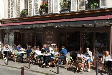 People sitting at a terrace of a bistro cafe and enjoying the April sun. Saint-Germain-des-Pres, Quartier Latin, Paris, France.